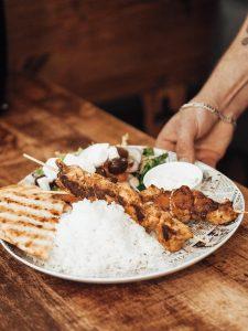 Middagstallerken med ris og kyllingspyd. Foto.