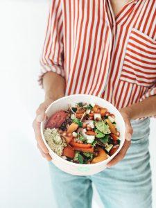 Jente som holder salatbolle. Foto.