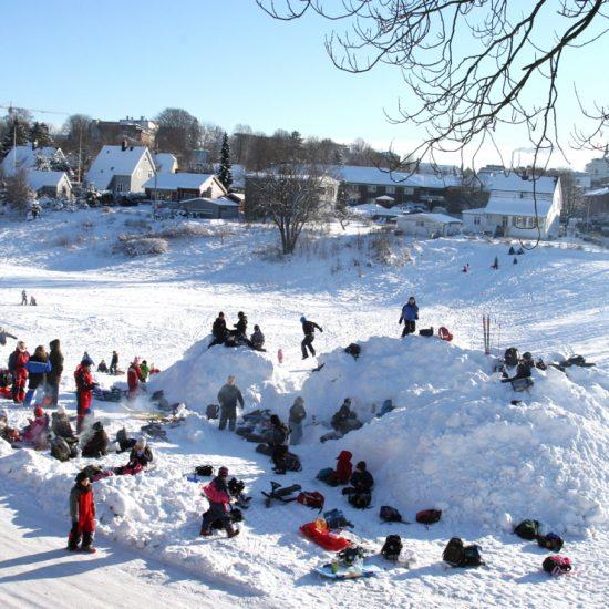 Barn som leger i snøen i Enenda. Foto