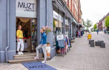 To mennesker utenfor en butikk i Sarpsborg. Foto.