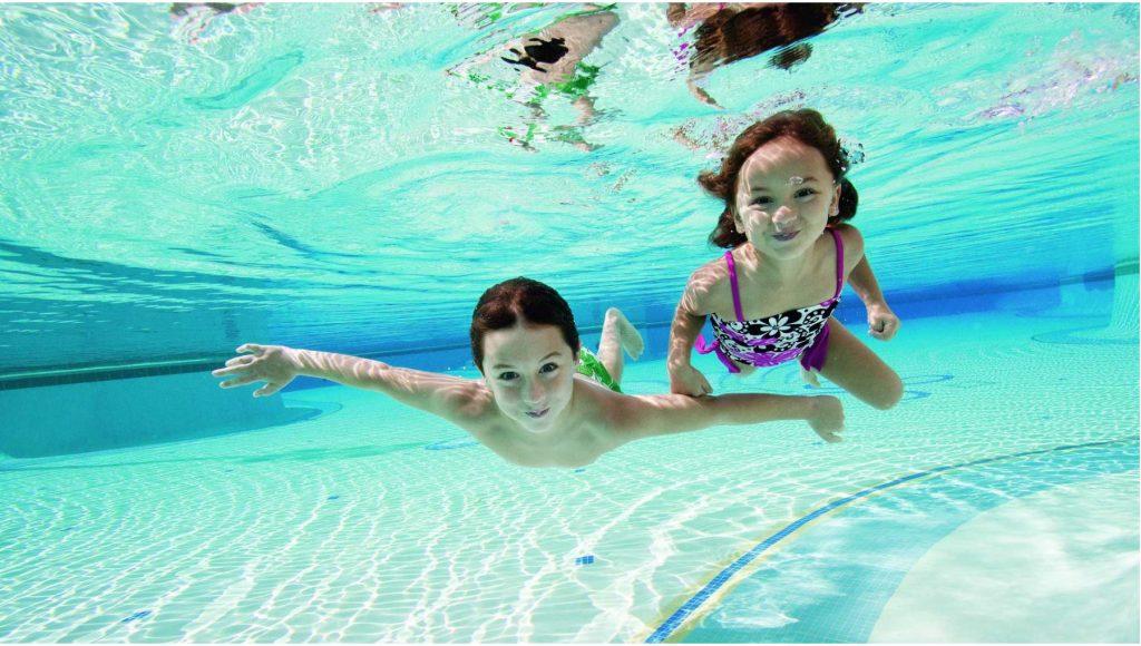 To barn som dykker i et basseng. Foto.