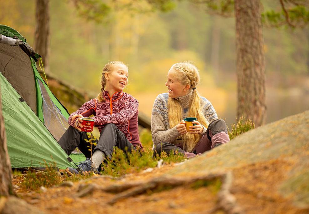 To jenter som sitter ved siden av et telt ved Børtevann i Sarpsborg. Foto.