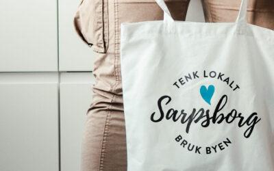 """Hender som holder et hvitt handlenett med påskriften """"Tenk lokalt - Sarpsborg - bruk byen. Foto."""