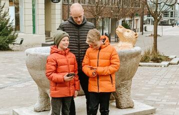 To gutter og en pappa spiller vandrespill på mobil i gågata i Sarpsborg. Foto.