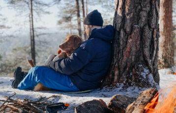 Mann og hund foran et bål i skogen. Foto.