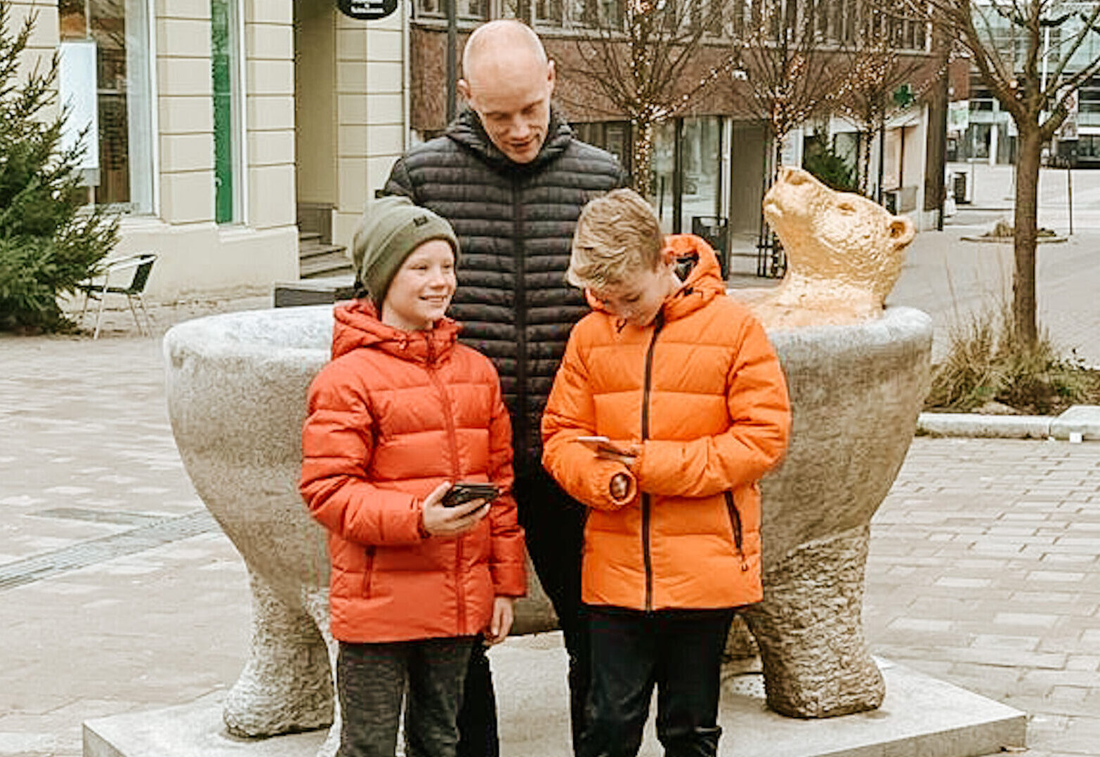 To gutter og en mann som står ved skulpturen Flod. Foto.