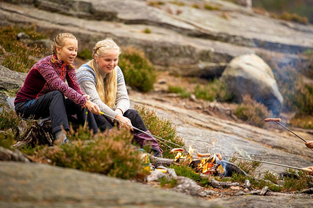 To jenter som griller pølser på et bål i skogen. Foto.