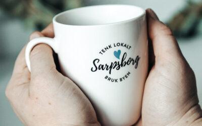 Hender som holder i en kaffekopp med påskriften: Sarpsborg, tenk lokalt, bruk byen. Foto.