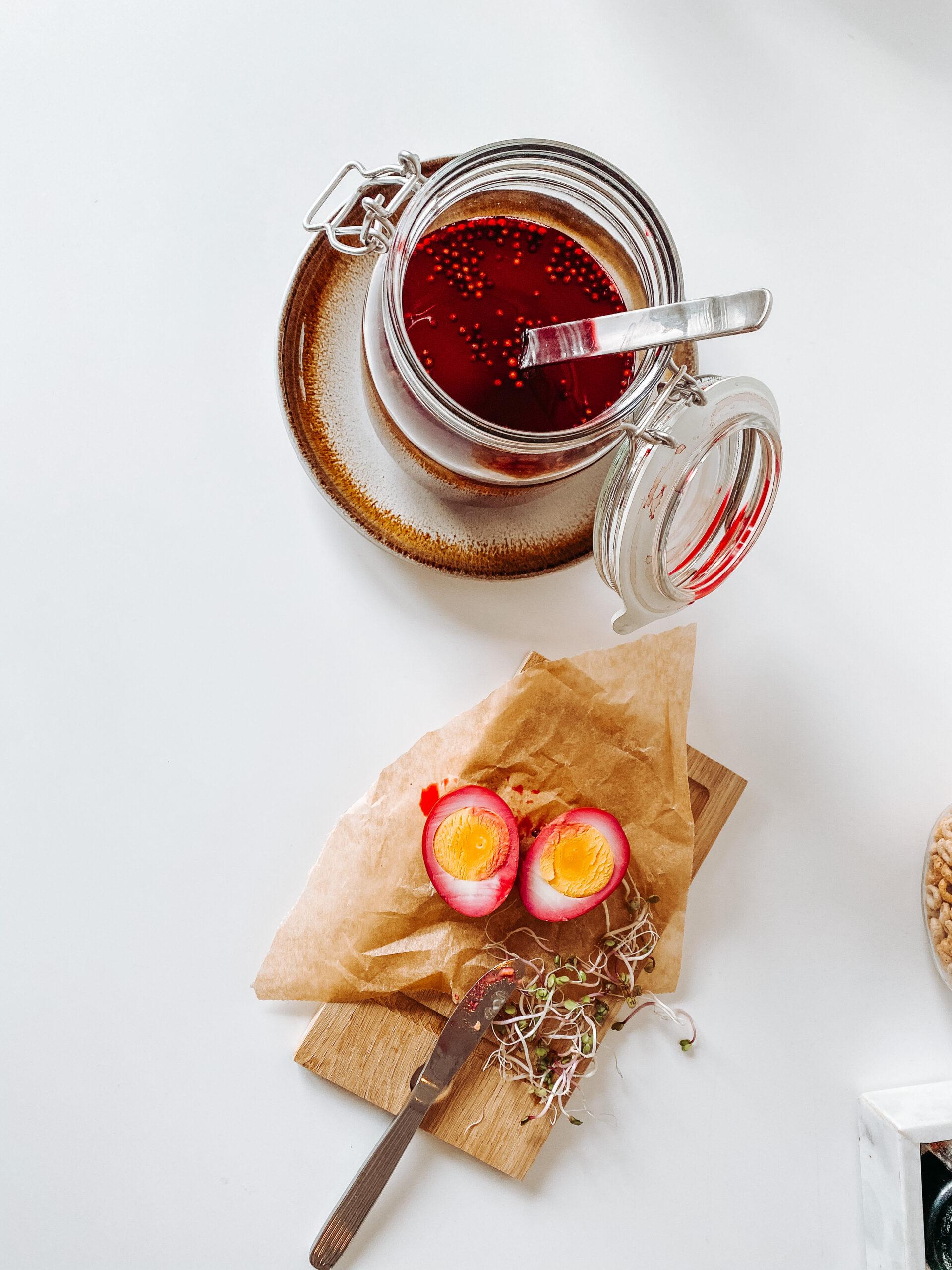 Kokt egg farget i rødbetsaft, bønnespirer og en kniv på ei fjøl. Ved siden av: Et norgesglass med rødbetsaft. Foto.