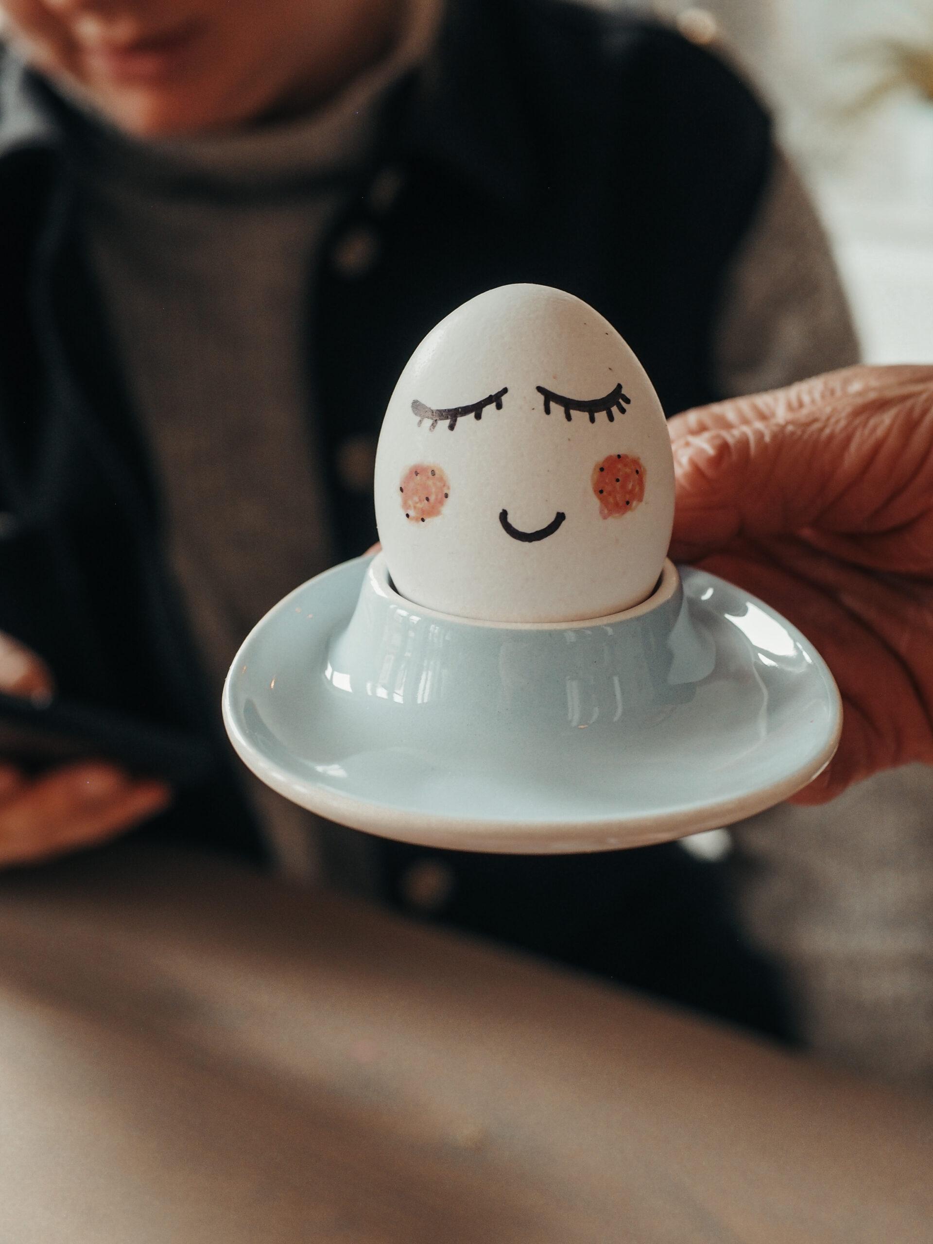 Egg med påmalt ansikt i eggeglass. Foto.