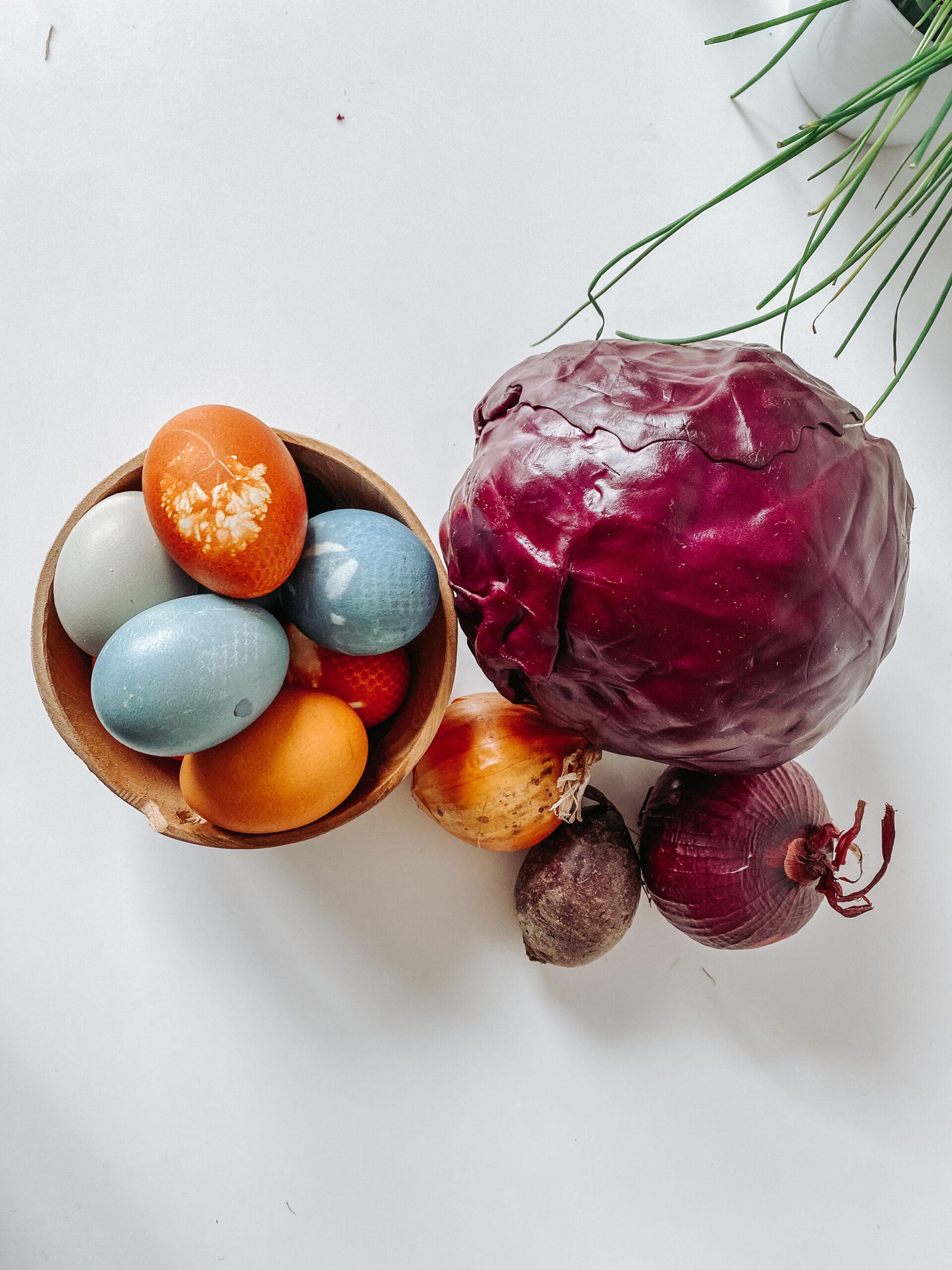 En kurv med flerfargede egg, rødkål og løk ved siden av. Foto.