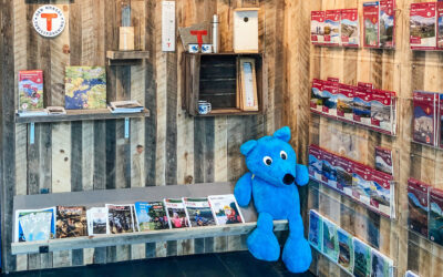 Den panelte DNT-veggen hos i Sarpsborg med diverse kart og produkter. Foto.