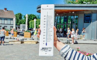 Hånd som holder Sarpetempen, med Sarpsborg torg i bakgrunnen. Foto.