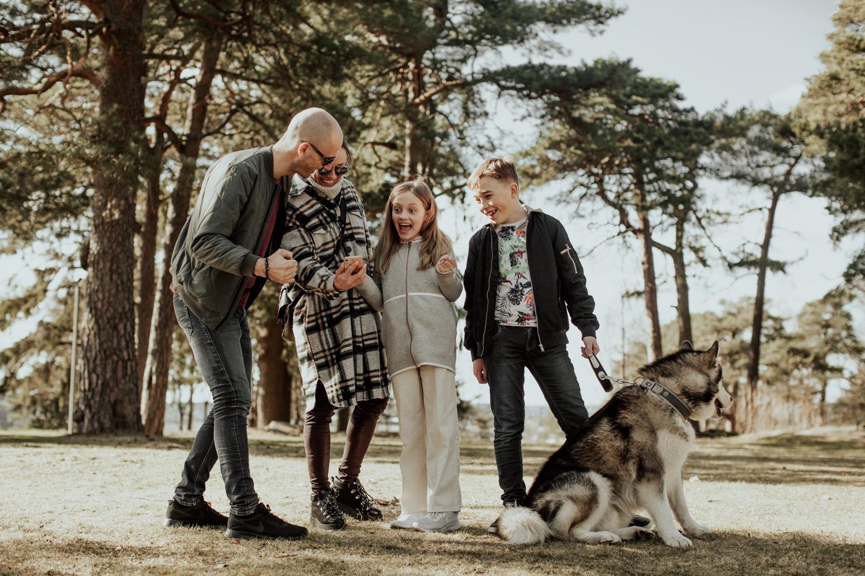 En familie på fire og hund spiller vandrespillet i Kulåsparken. Foto.