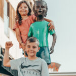 Barn som står oppe på en skulptur i gågata i Sarpsborg. Foto.