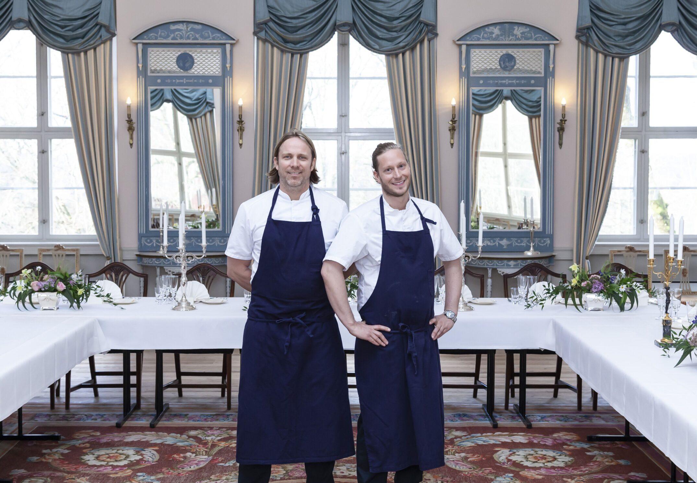 To kokker ved dekkede langbord på Hafslund Hovedgård. Foto.